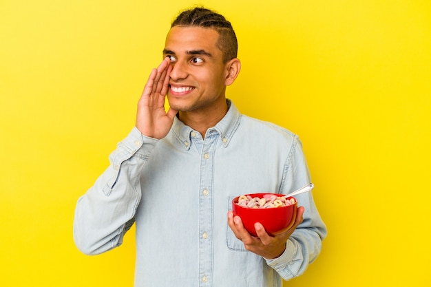 Young venezuelan man holding a cereals bowl isolated on yellow background shouting and holding palm near opened mouth.