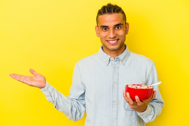 Young venezuelan man holding a cereals bowl isolated on yellow background showing a copy space on a palm and holding another hand on waist.