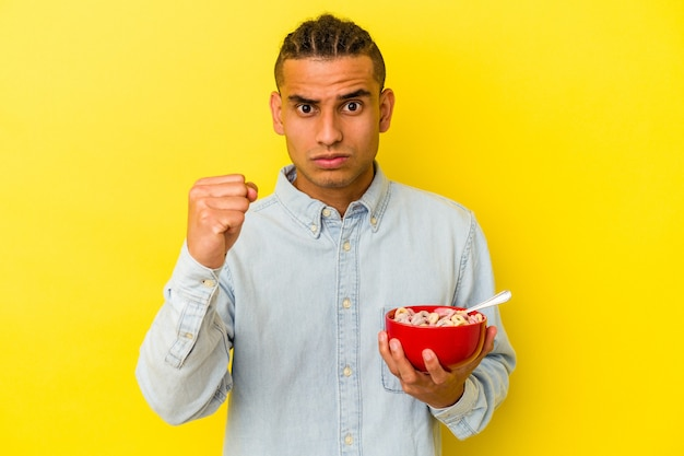 Young venezuelan man holding a cereals bowl isolated on yellow background showing fist to camera