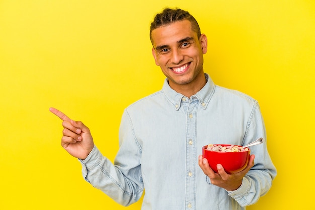 Young venezuelan man holding a cereals bowl isolated on yellow background smiling and pointing aside