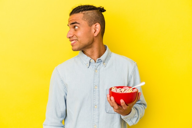 Young venezuelan man holding a cereals bowl isolated on yellow background