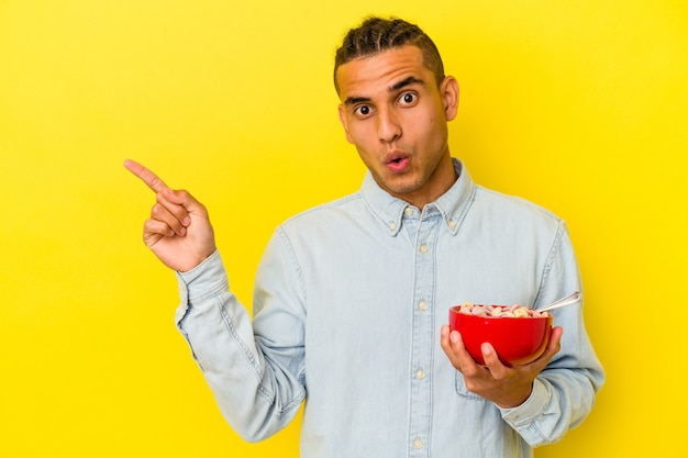 Young venezuelan man holding a cereals bowl isolated on yellow wall pointing to the side