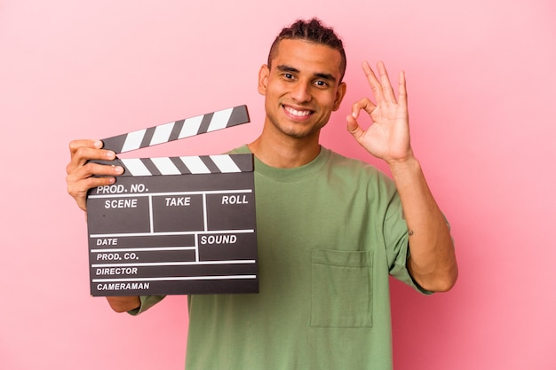 Young venezuelan man holding a clapperboard isolated on pink background cheerful and confident showing ok gesture.