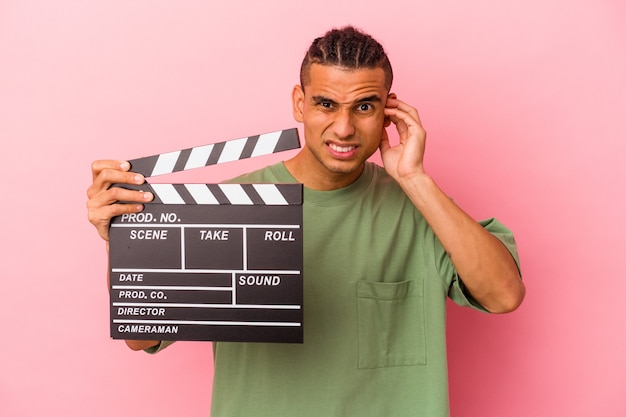Young venezuelan man holding a clapperboard isolated on pink background covering ears with hands.