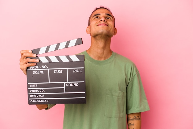 Young venezuelan man holding a clapperboard isolated on pink background dreaming of achieving goals and purposes
