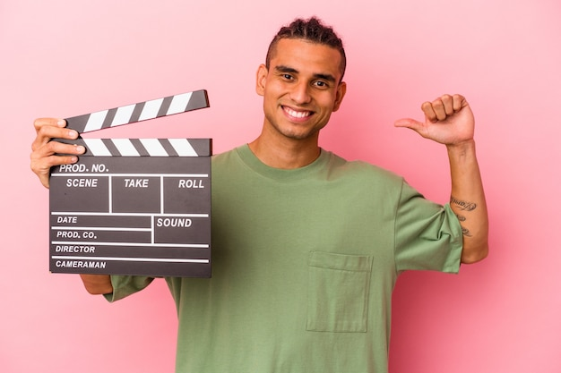 Young venezuelan man holding a clapperboard isolated on pink background feels proud and self confident, example to follow.