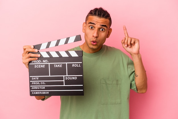 Young venezuelan man holding a clapperboard isolated on pink background having an idea, inspiration concept.