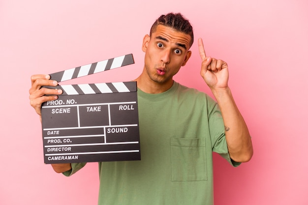Young venezuelan man holding a clapperboard isolated on pink background having some great idea, concept of creativity.
