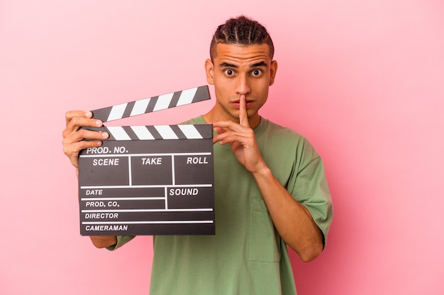 Young venezuelan man holding a clapperboard isolated on pink background keeping a secret or asking for silence.
