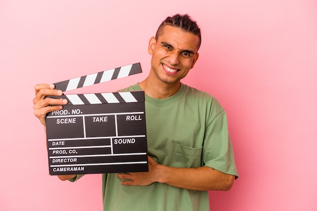 Young venezuelan man holding a clapperboard isolated on pink background laughing and having fun.