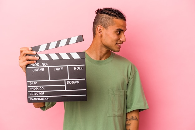 Young venezuelan man holding a clapperboard isolated on pink background looks aside smiling, cheerful and pleasant.