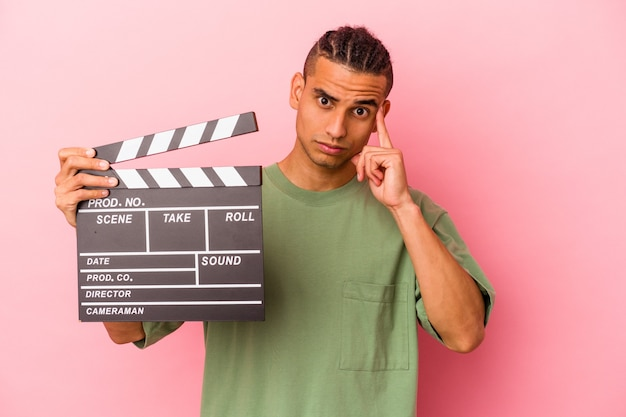 Young venezuelan man holding a clapperboard isolated on pink background pointing temple with finger, thinking, focused on a task.
