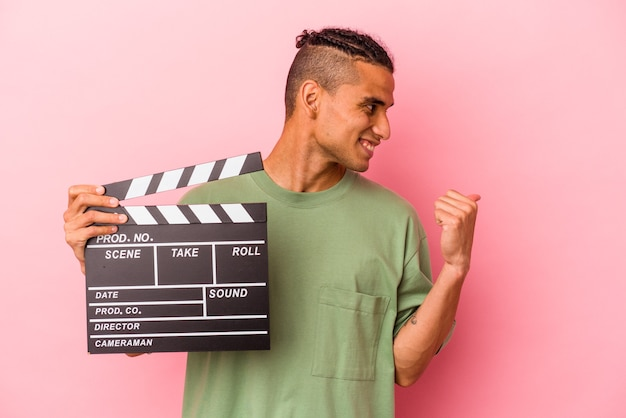 Young venezuelan man holding a clapperboard isolated on pink background points with thumb finger away, laughing and carefree.