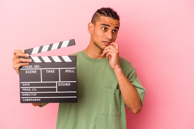 Young venezuelan man holding a clapperboard isolated on pink background relaxed thinking about something looking at a copy space.