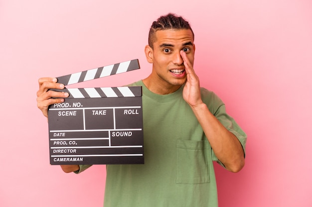 Young venezuelan man holding a clapperboard isolated on pink background shouting and holding palm near opened mouth.