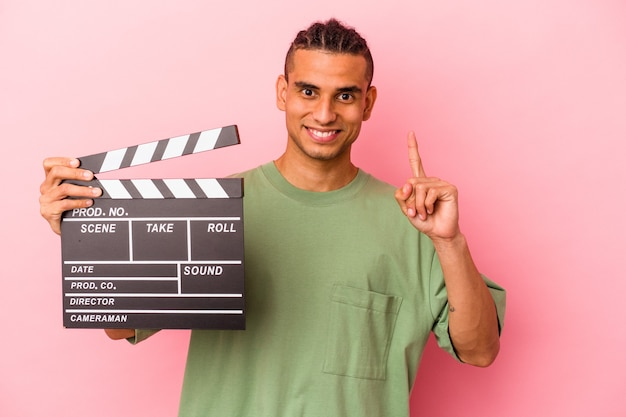 Young venezuelan man holding a clapperboard isolated on pink background showing number one with finger.