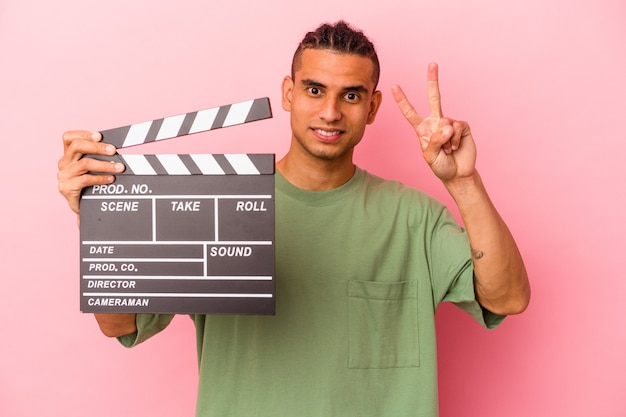 Young venezuelan man holding a clapperboard isolated on pink background showing number two with fingers.