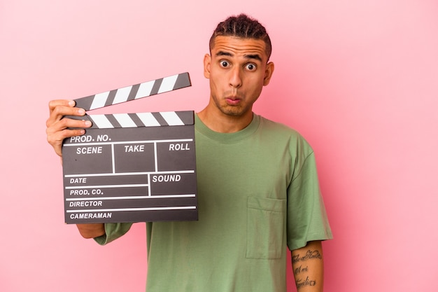 Young venezuelan man holding a clapperboard isolated on pink background shrugs shoulders and open eyes confused.