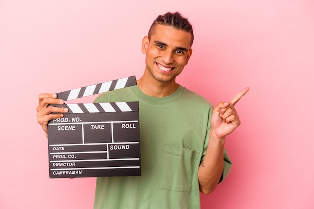 Young venezuelan man holding a clapperboard isolated on pink background smiling and pointing aside, showing something at blank space.