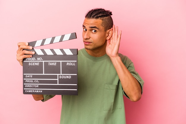 Young venezuelan man holding a clapperboard isolated on pink background trying to listening a gossip.