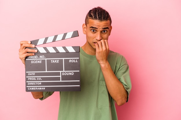 Young venezuelan man holding a clapperboard isolated on pink wall biting fingernails, nervous and very anxious.