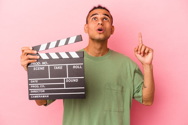 Young venezuelan man holding a clapperboard isolated on pink wall pointing upside with opened mouth.