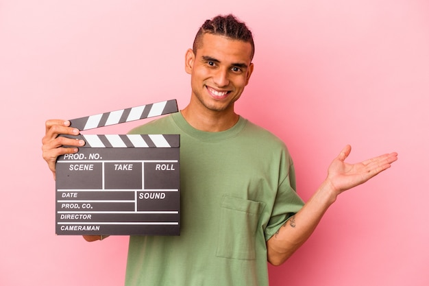 Young venezuelan man holding a clapperboard isolated on pink wall showing a copy space on a palm and holding another hand on waist.