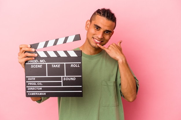 Young venezuelan man holding a clapperboard isolated on pink wall showing a mobile phone call gesture with fingers.