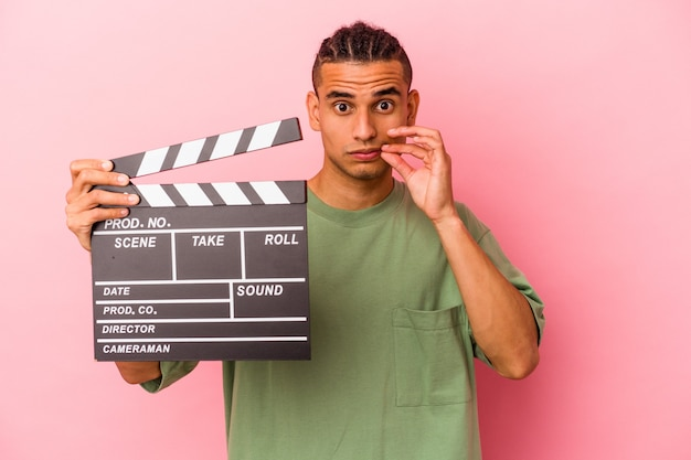 Young venezuelan man holding a clapperboard isolated on pink wall with fingers on lips keeping a secret.