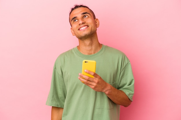Young venezuelan man holding a mobile phone isolated on pink wall dreaming of achieving goals and purposes