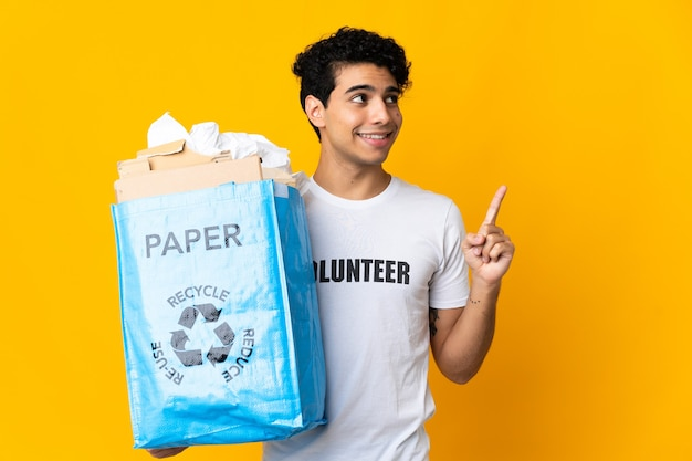 Young venezuelan man holding a recycling bag full of paper to recycle pointing up a great idea