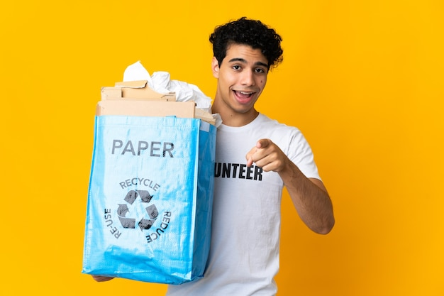 Young venezuelan man holding a recycling bag full of paper to recycle surprised and pointing front