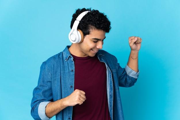 Молодой венесуэльский мужчина изолирован на синем, слушает музыку и танцует