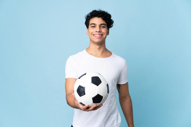 サッカーボールで青に分離された若いベネズエラの男
