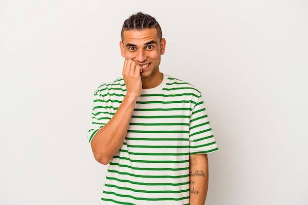 흰색 배경에 격리된 젊은 베네수엘라 남자는 손톱을 물어뜯고 긴장하고 매우 불안해합니다.