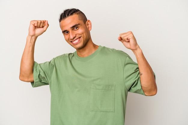 Молодой венесуэльский мужчина, изолированные на белом фоне, празднует особый день, прыгает и поднимает руки с энергией.