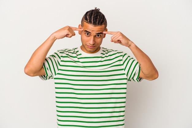 Молодой венесуэльский мужчина, изолированные на белом фоне, сосредоточился на задаче, держа указательные пальцы, указывая головой.