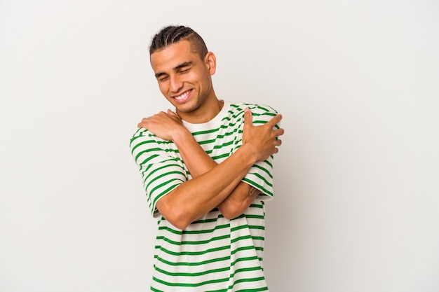 白い背景の抱擁に分離された若いベネズエラの男は、のんきと幸せに笑っています。