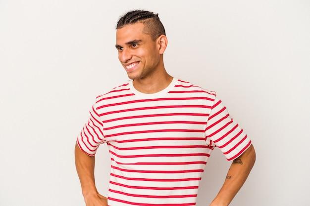白い背景で隔離された若いベネズエラの男は笑って目を閉じ、リラックスして幸せを感じます。