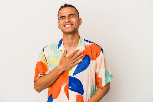 白い背景で隔離された若いベネズエラの男は、胸に手を置いて大声で笑います。