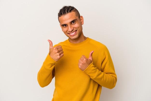 Молодой венесуэльский мужчина, изолированные на белом фоне, поднимает пальцы вверх, улыбается и уверенно.