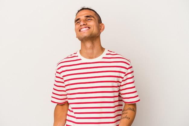 Молодой венесуэльский мужчина, изолированные на белом фоне, расслабленный и счастливый смех, вытянув шею, показывая зубы.