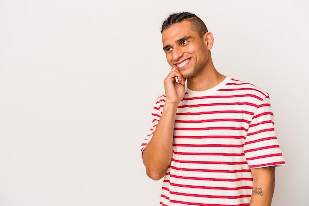 Молодой венесуэльский мужчина, изолированных на белом фоне, расслабился, думая о чем-то, глядя на копию пространства.