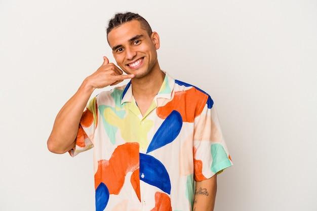 指で携帯電話の呼び出しジェスチャーを示す白い背景で隔離の若いベネズエラの男。