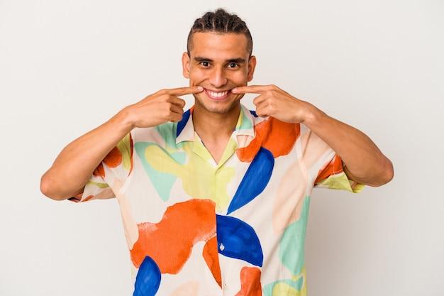 Молодой венесуэльский мужчина на белом фоне улыбается, указывая пальцами на рот.
