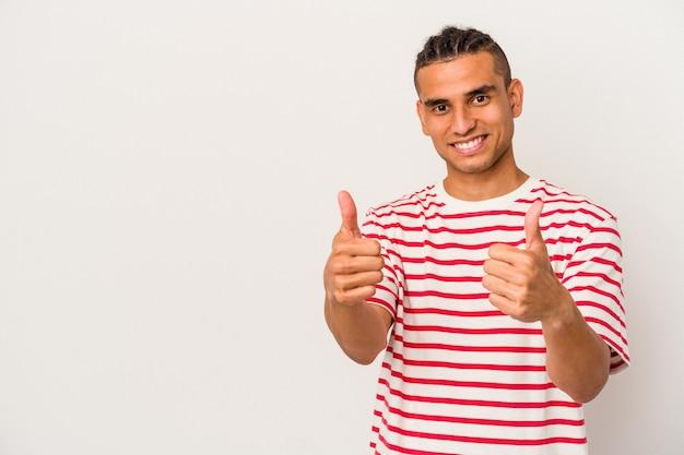 Молодой венесуэльский мужчина, изолированные на белом фоне, улыбается и поднимает палец вверх
