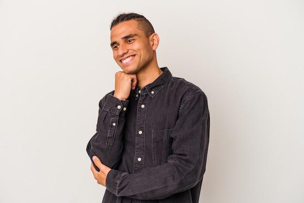 Молодой венесуэльский мужчина, изолированных на белом фоне, улыбается, счастлив и уверен, трогательно подбородок рукой.