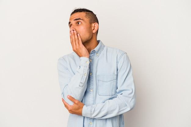 手で口を覆う疲れたジェスチャーを示すあくびをしている白い背景に分離された若いベネズエラの男。