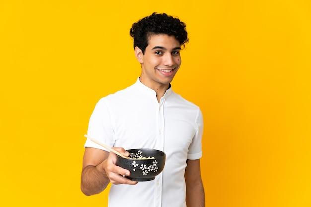 箸で麺のボウルを保持しながら幸せな表情で黄色の背景に分離された若いベネズエラの男