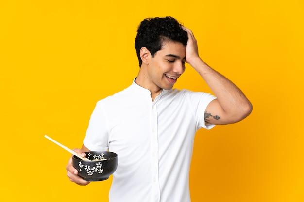黄色で隔離された若いベネズエラの男は、箸で麺のボウルを保持しながら何かを実現し、解決策を意図しています